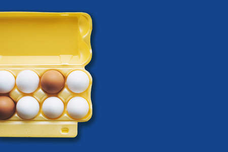 White and brown eggs in a yellow half box on a yellow background