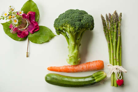 carot: flat lay bgreen vegetables with yellow carot on white background