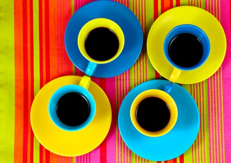 cup four: flat lay coffee four color bright cups with different bright plates under them on colored background