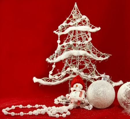 stock photo white christmas tree and decorations with toy snowman at the red background