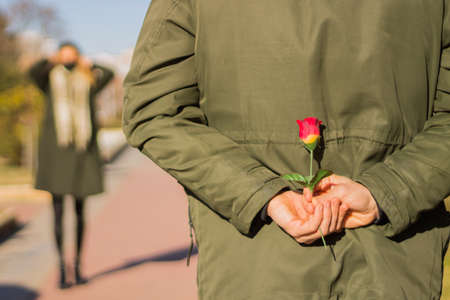 Close-up of a man's hands hiding a rose with a woman out of focus in the distance