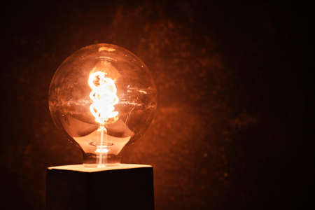 an incandescent led light with a dark background - idea concept