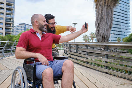Carer Pushing Senior Man In Wheelchair - people with disabilites concept