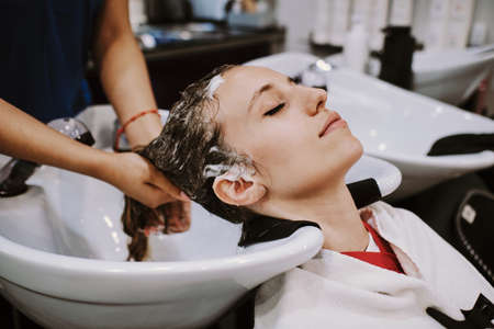 beauty and people concept - happy young woman with hairdresser washing head at hair salon Stockfoto