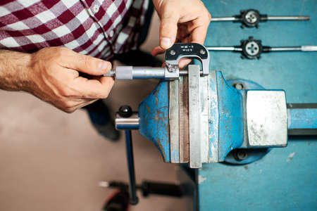 a worker measures with a micrometer in his workshop