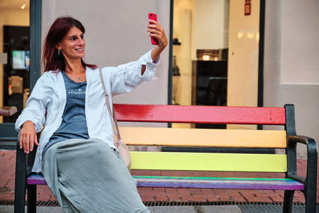 adult woman using mobile phone sitted on LGTBQ bench 写真素材