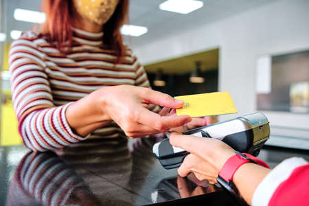 woman with protective mask using credit card to pay contactless