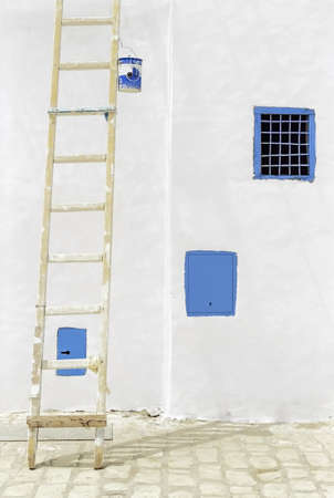 Painting a wall in a sunny day in Tunisia.