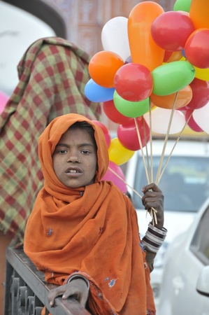 In Jaipur many boys and girls work and live in the streets. They can not go to school and to sell anything is the only way to survive in India. This photo was taken in Ajmeri gate in Jaipur in 3-12-2010.  Stock Photo - 9205523