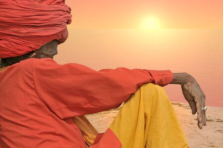 poorness: Holy man in the sunset near Ganges, India.