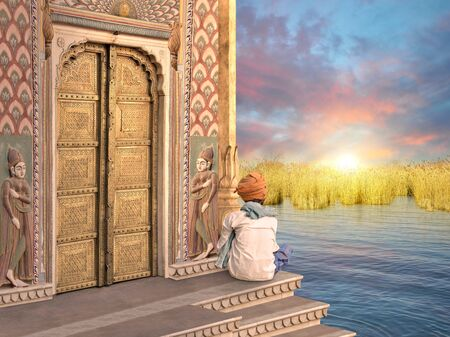 Traditional Indian man near a door in the sunrise.