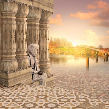 Old man on the traditional indian columns in the sunset. Stock Photo