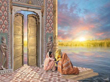 Women near a traditional indian door in the sunrise.