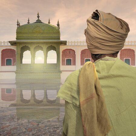 poor man: Pobre hombre cerca de un palacio indio en la niebla.