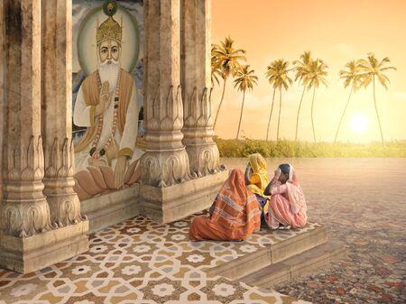 mujeres orando: Mujeres hind�es rezando en el para�so en la puesta del sol.