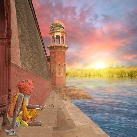 sadhu: Indian sadhu reading a religious book on the Ganges. Stock Photo