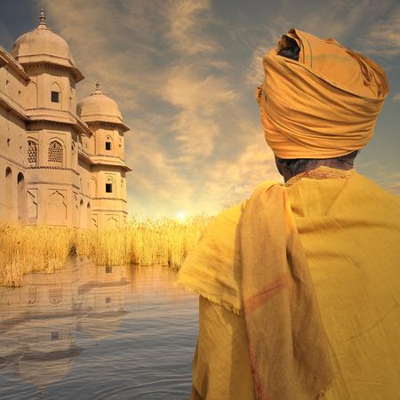 hombre pobre: Pobre hombre cerca de torres de indios en la puesta de sol.