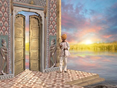 Man near a traditional indian door in the sunrise.