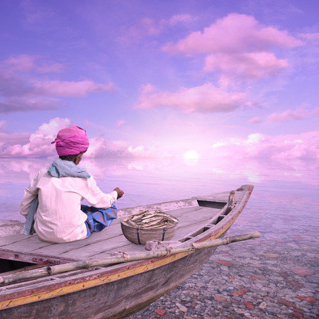 Indian fisherman in his boat working in the paradise. Stock Photo