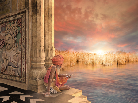 sadhu: Sadhu reading near Ganges river in the sunset. Stock Photo
