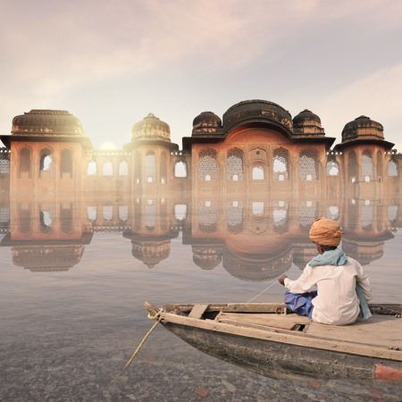 Indian fisherman near a palace in the mist. Stock Photo