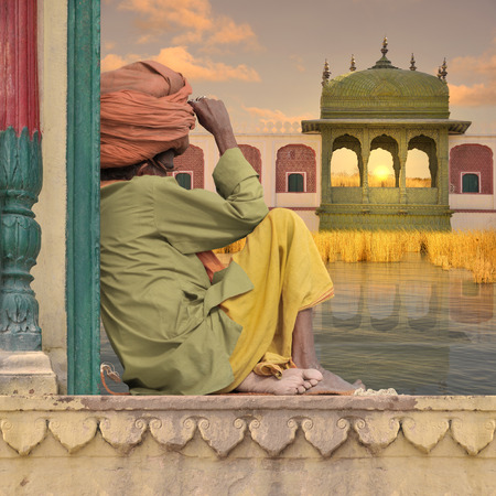 Holy man near a luxurious palace on the Ganges. Stock Photo