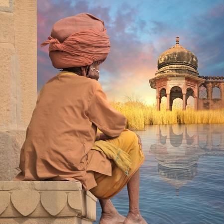 sadhu: Sadhu near indian lake during the sunrise.