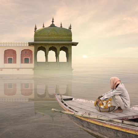 Indian man with flowers sailing in the mist. Stock Photo