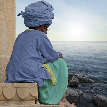 sadhu: Sadhu meditating near indian coast during the sunrise. Stock Photo