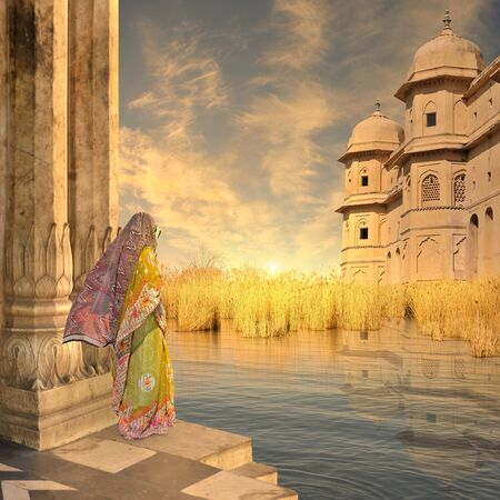 Woman near typical indian architecture in the sunset. Stock Photo