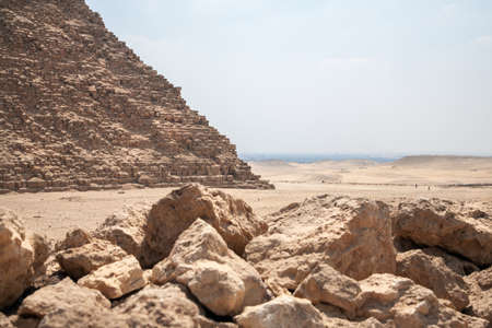Parth of pyramid Cheops in Giza plato with many stones on foreground and view desert and Cairo, capital of Egypt, on backgound Stok Fotoğraf