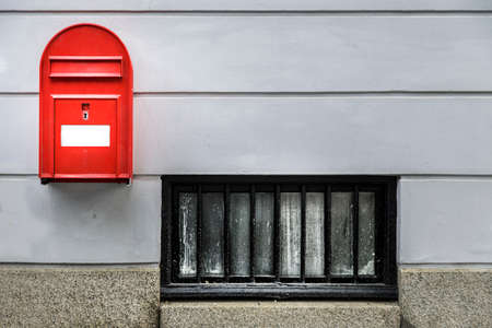 A red postbox on a white wall in a street in Copenhagen
