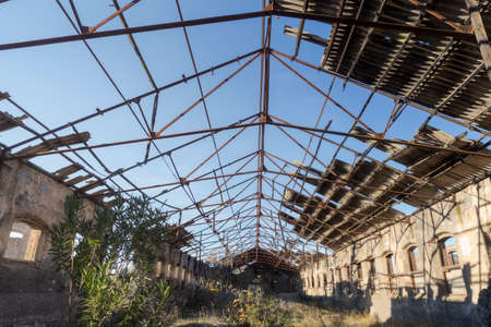 An old warehouse of an abandoned factory with the roof demolished