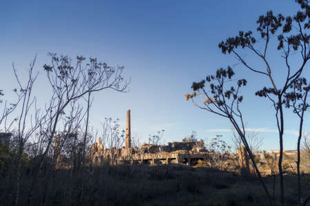 Exterior of an abandoned place with the ruins of a factory in the background of the image during a sunny afternoon
