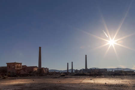 Intense midday sun falls on the barren ground of an abandoned factory