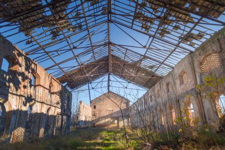 Interior of an old abandoned warehouse with the roof demolished by the passage of time