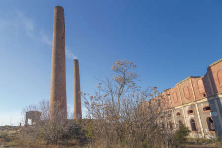 Chimneys of an old abandoned factory during a sunny afternoon