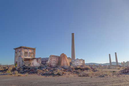 Buildings and chimneys of an old abandoned factory during a sunny afternoon in southern Spain