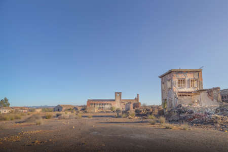 Wasteland of an abandoned place with some ruined buildings of an old factory Imagens