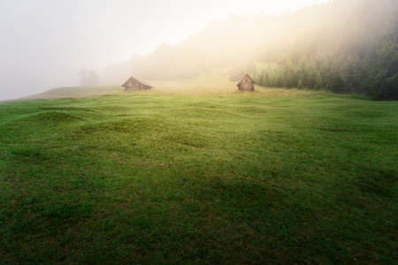 Two cabins in an area of the Bavarian Alps during a misty summer dawn Imagens
