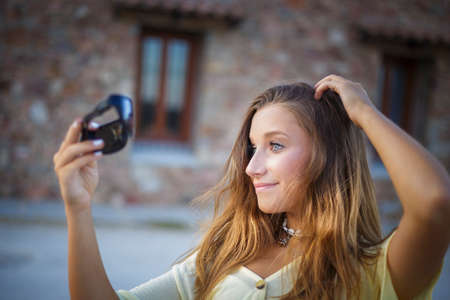 A Fourteen year-old teenage girl holds sunglasses as a mirror to retouch her hair in an outdoor photo shoot during a summer evening