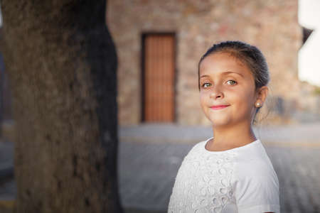 An eight year old girl looks at the camera and smiles in an outdoor photo shooting during a summer evening
