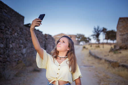 A fourteen-year-old teenager seeks coverage on her smartphone in a rural area Banco de Imagens