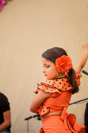 Little child dancing spanish dance named Flamenco. Small girl in an orange gipsy costume n Cordoba, Spain. Imagens
