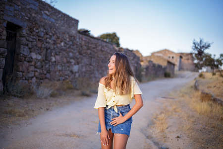 Pretty teen girl ina a yellow blouse and a denim skirt laughing. A stone wall background