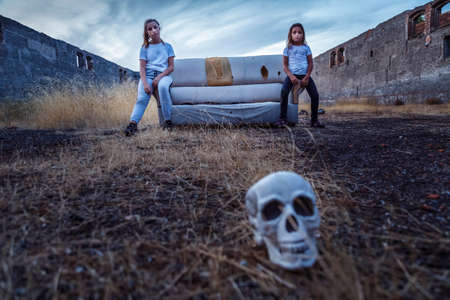 Fourteen-year-old teenager and little girl of eight posing on a couch in an old abandoned factory. Outdoor photo session at sunset during blue hour