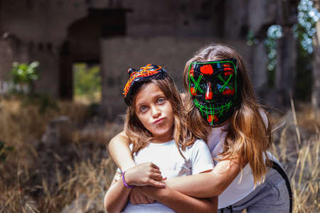 Two girls looking at camera with masks**Fourteen-year-old teenager and eight-year-old girl posing with sinister masks. Outdoors shooting in an abandoned building. Blurry background. A softbox helps illuminate the scene
