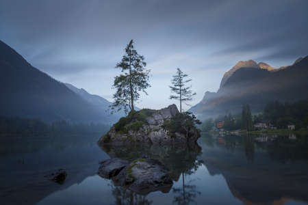 Spectacular, beautiful sunrise over Lake in Germany. Two pine trees growing on a big stone.