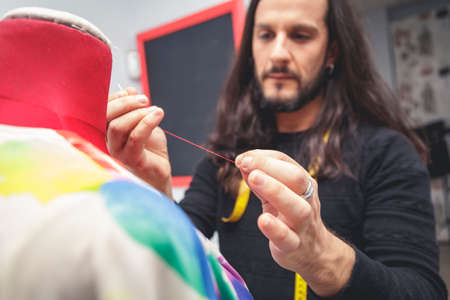 Dressmaker in a sewing workshop. Long-haired young man holding a red thread in front of a mannequin. Selective focus