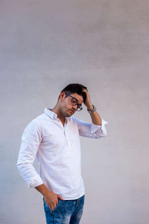 Doubtful young man wearing glasses and white shirt touches his hair. Light background Archivio Fotografico